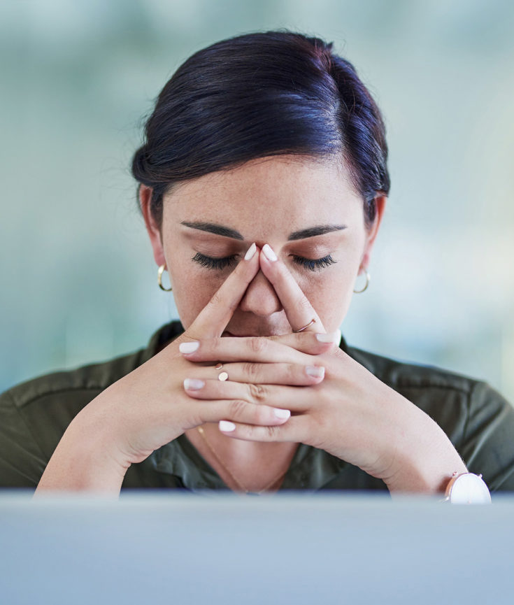 Photo of woman in front of computer with hands to her face