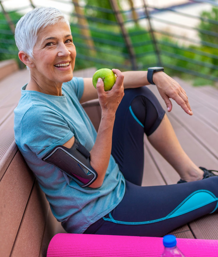 Photo of older woman eating an apple